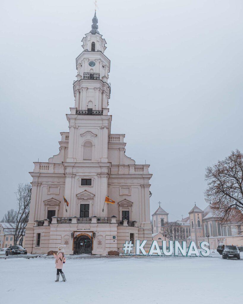 O chão todo coberto de neve circundando o prédio da Prefeitura, com o letreiro de Kaunas localizado bem em frente.