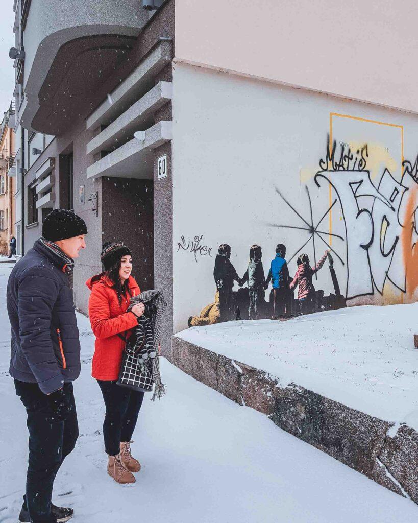 Marjorie e o guia do Visit Kaunas andando pelas ruas cobertas de neve da cidade. O guia está mostrando à ela uma parede grafitada que representa 4 crianças.