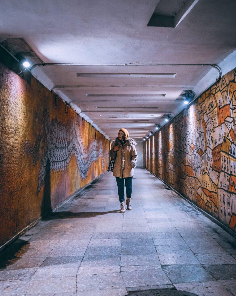 Majorie andando por um túnel iluminado em Kaunas. As pinturas nas paredes dos dois lados do túnel são todas em tons alaranjados, como exemplo de várias casas em uma delas.